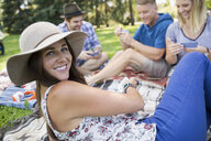 Portrait smiling woman playing cards with friends in summer park - HEROF13852