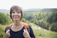 Portrait smiling mature woman with backpack hiking on sunny remote rural hillside - HEROF13861