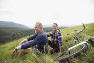 Portrait smiling senior couple relaxing near mountain bikes in remote rural field - HEROF13864