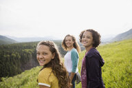 Portrait smiling teenage sisters in remote rural field - HEROF13867