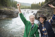 Portrait playful senior couple cheering at waterfall - HEROF13870