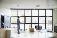 Pensive businessman looking through conference room window - HEROF13888
