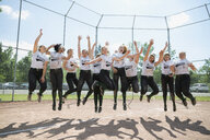 Portrait cheering middle school girl softball team jumping on baseball diamond - HEROF13897