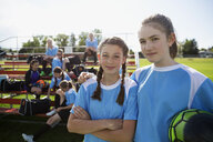 Portrait confident middle school girl soccer players near bleachers - HEROF13903
