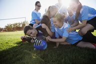 Playful middle school girl soccer team celebrating in pile on sunny field - HEROF13906