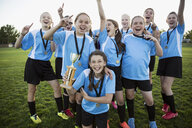 Portrait exuberant middle school girl soccer team celebrating and cheering with trophy - HEROF13909