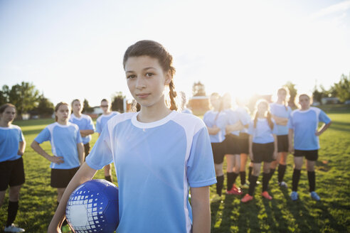 Portrait confident middle school girl soccer player showing attitude with teammates on sunny field - HEROF13912