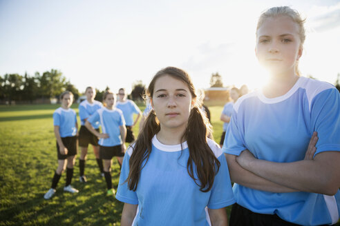 Portrait confident middle school girl soccer players showing attitude with teammates on sunny field - HEROF13915