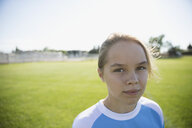 Portrait confident middle school girl soccer player on sunny field - HEROF13918