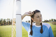 Pensive middle school girl soccer player leaning on goal net post looking away - HEROF13921