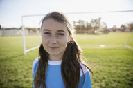 Portrait confident middle school girl soccer player on sunny field - HEROF13924