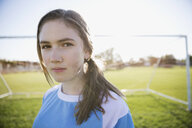Portrait confident middle school girl soccer player showing attitude on sunny field - HEROF13927