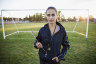 Portrait confident soccer coach with clipboard on field - HEROF13936
