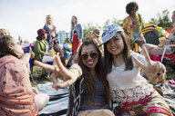 Portrait enthusiastic young women gesturing peace sign at summer music festival - HEROF13939