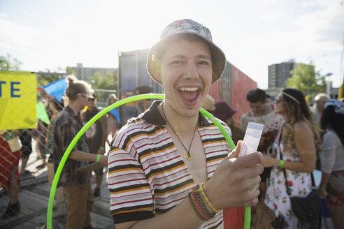 Portrait enthusiastic young man with plastic hoop showing summer music festival ticket outside entrance - HEROF13945
