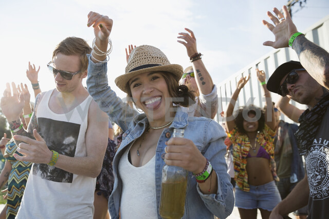 Portrait enthusiastic young woman dancing and drinking beer with friends at summer music festival - HEROF13948 - Hero Images/Westend61