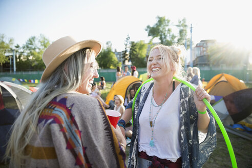 Playful young women with plastic hoop at summer music festival campsite - HEROF13963