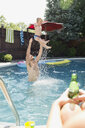 Playful father throwing son overhead in swimming pool - HEROF13978