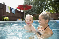 Portrait laughing mother and son in swimming pool - HEROF13984