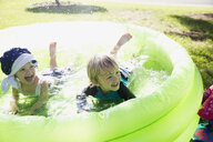 Playful brother and sister in wading pool in sunny backyard - HEROF13987