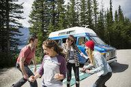 Playful friends dancing outside camper van at remote lakeside - HEROF14008