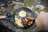 Personal perspective woman cooking bacon and eggs in camping skillet - HEROF14014