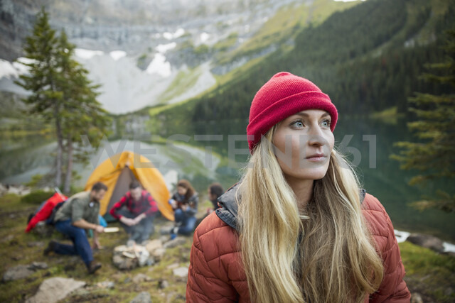 Pensive woman camping with friends looking away - HEROF14017