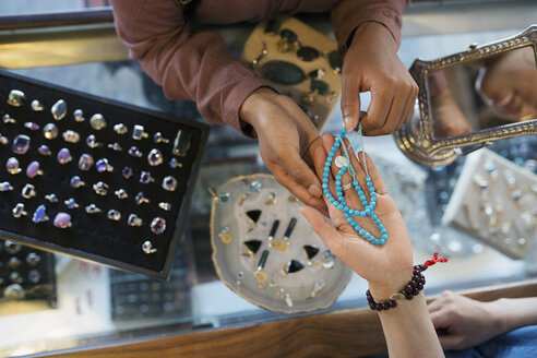 Overhead view women browsing necklace at jewelry counter in shop - HEROF14023