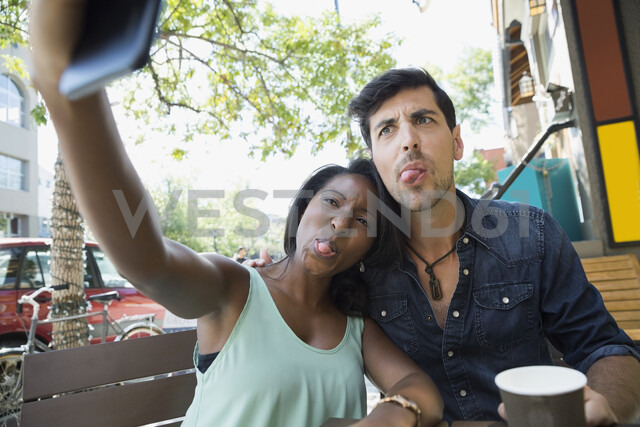 Playful couple making silly faces and taking selfie with camera phone at sidewalk cafe - HEROF14029