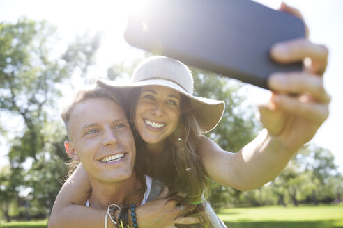 Playful couple piggybacking taking selfie with camera phone in sunny summer park - HEROF14044