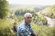 Portrait confident mature man hiking resting at sunny remote rural hilltop - HEROF14053