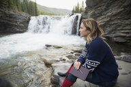 Pensive woman with journal at waterfall - HEROF14056