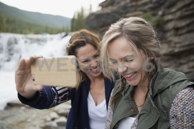 Playful women friends laughing taking selfie with camera phone near waterfall - HEROF14059 - Hero Images/Westend61