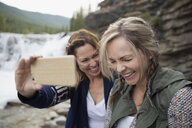 Playful women friends laughing taking selfie with camera phone near waterfall - HEROF14059