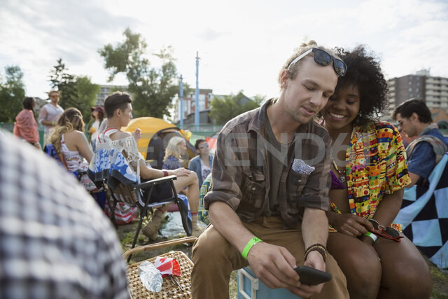Young couple texting at summer music festival campsite - HEROF14071 - Hero Images/Westend61