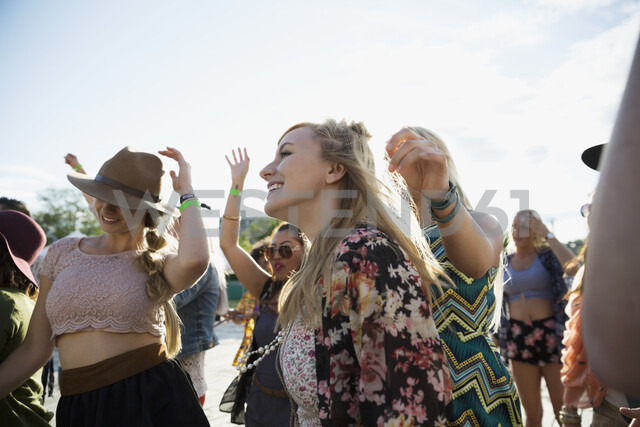 Young women dancing in crowd at summer music festival - HEROF14092 - Hero Images/Westend61