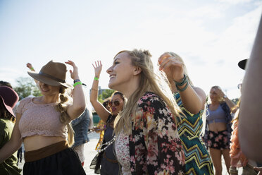 Young women dancing in crowd at summer music festival - HEROF14092