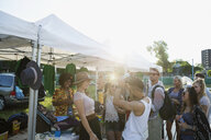 Young men and women at booth at summer music festival - HEROF14095