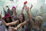 Young women cheering in powder crowd at summer music festival - HEROF14110