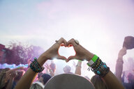 Woman forming heart-shape with hands in crowd at summer music festival - HEROF14119