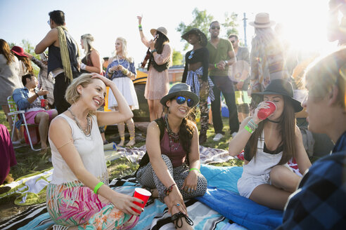 Young friends drinking and hanging out at summer music festival campsite - HEROF14128