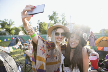Young women taking selfie at summer music festival campsite - HEROF14137