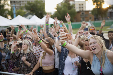 Young women taking selfie in crowd at summer music festival - HEROF14146