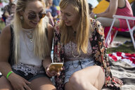 Young women with cell phone at summer music festival campsite - HEROF14149