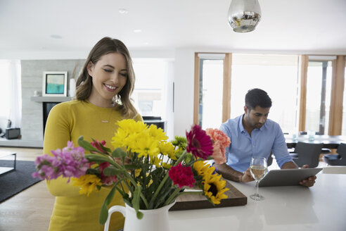 Young couple arranging flowers and using digital tablet in kitchen - HEROF14170