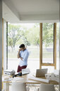 Young man talking on cell phone working in dining room - HEROF14173