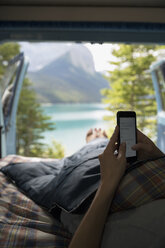 Woman using cell phone laying in back of camper van with remote lake view - HEROF14191