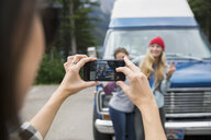 Woman with camera phone photographing friends outside camper van - HEROF14197