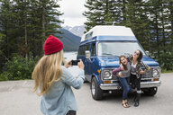 Woman with camera phone photographing friends outside camper van at lakeside - HEROF14200