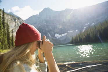 Woman with digital camera photographing remote sunny mountain lake view - HEROF14206
